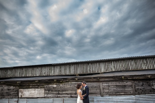 Bride and groom outside barn at Packington Moor