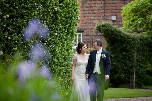 Bride and groom walking in grounds of Packington Moor