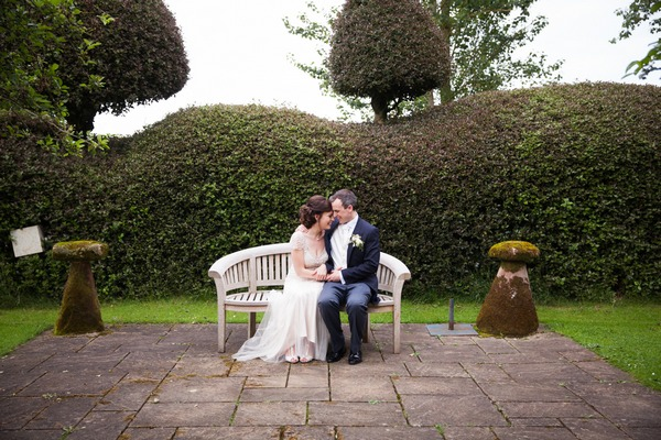 Bride and groom sitting on bench at Packington Moor
