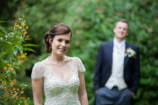 Bride with groom out of focus in background