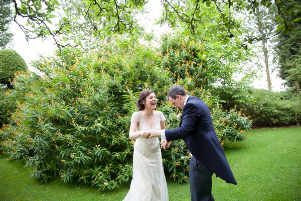 Bride and groom laughing in grounds of Packington Moor