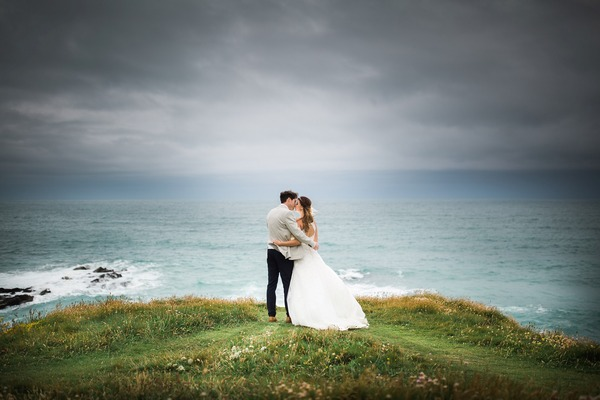 Bride and groom kissing on hill overlooking the sea - Picture by Toby Lowe Photography