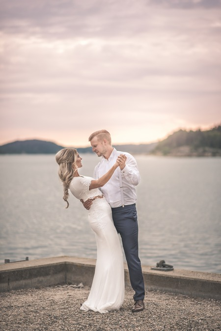 Bride and groom holding each other next to water - Picture by Natalie Johansson Fotograf