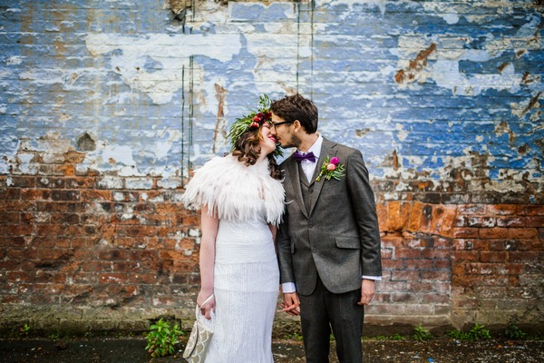 Bride and groom kissing in front of a wall - Picture by Sarah Janes Photography