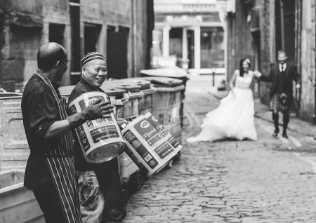 Men playing empty oil drums as bride and groom walk down cobbled street - Picture by Chris Scott Photography