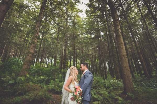 Bride and groom standing in front of tall trees - Picture by Lee Maxwell Photography