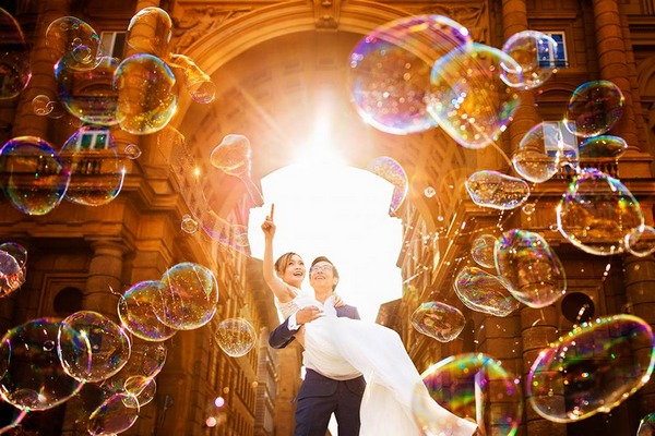 Groom carrying bride as she points at bubbles floating in the air - Picture by Fabio Mirulla Photographer