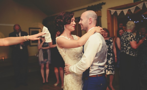 Someone holding out a tissue as bride and groom have their first dance - Picture by Silvery Moon Photography