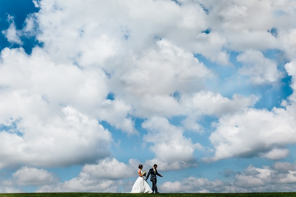 Bride and groom walking with lots of clouds in background - Picture by James Andrew Photography