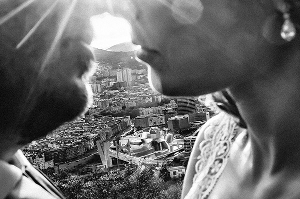 Close up of bride and groom's faces about to kiss in front of city - Picture by Javi Collazo Fotógrafo
