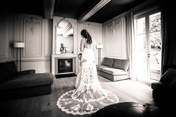 Flower girl hugging bride in lace wedding dress with long train - Picture by Cinderella Photographie