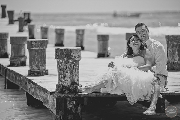 Bride and groom sitting on jetty