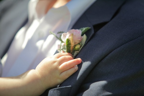 Baby's hand touching buttonhole
