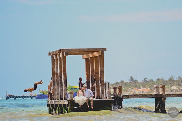 Bride and groom kissing on end of jetty as man jumps off