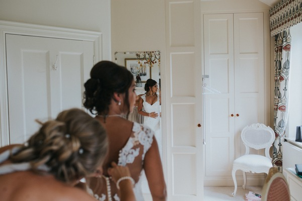 Bridesmaid doing up back of bride's wedding dress