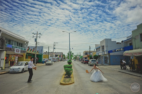 Bride and groom playing tennis in middle of street in Mexico