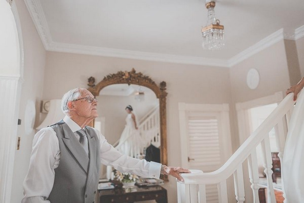 Reflection in mirror of bride walking down stairs as father waits at the bottom - Picture by Michelle Lindsell Photography