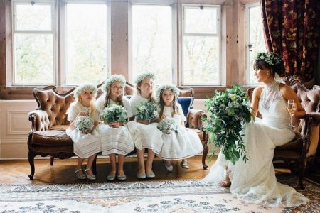 Flower girls sitting on couch next to bride in chair - Picture by Helen Russell Photography