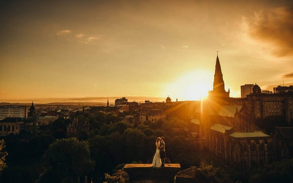 Bride and groom standing on plinth with view over Glasgow at sunset - Picture by Neil Thomas Douglas Photography