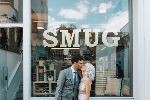 Bride and groom kissing in front of window with SMUG written on it - Picture by Miss Gen Photography