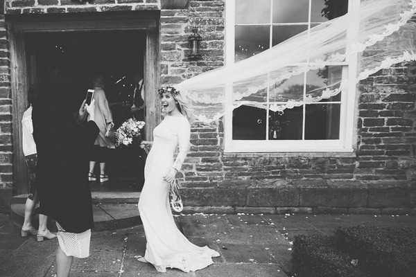 Bride having her picture taken by wedding guest as long veil blows in wind - Picture by Philippa James Photography