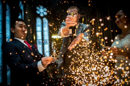 Wedding guests holding bottle of Champagne with explosion of sparks in front of them - Picture by James Tracey Photography