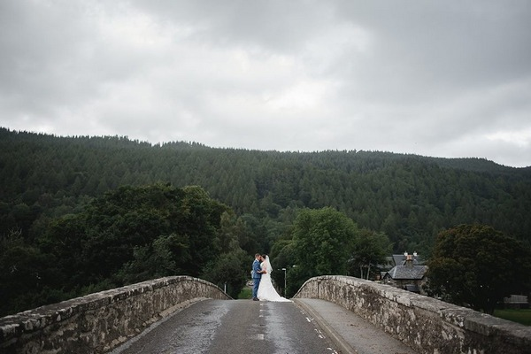 Bride and groom standing in middle of bridge - Picture by Mack Photo