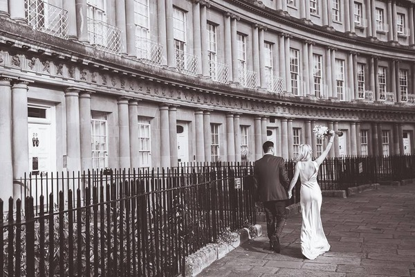 Bride holding bouquet in air as she walks past row of houses with groom - Picture by Steph Newton Photography