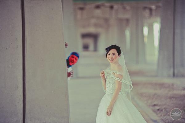 Groom wearing devil balaclava peering out from pillar behind bride