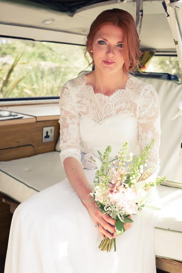 Bride holding bouquet in back of camper van
