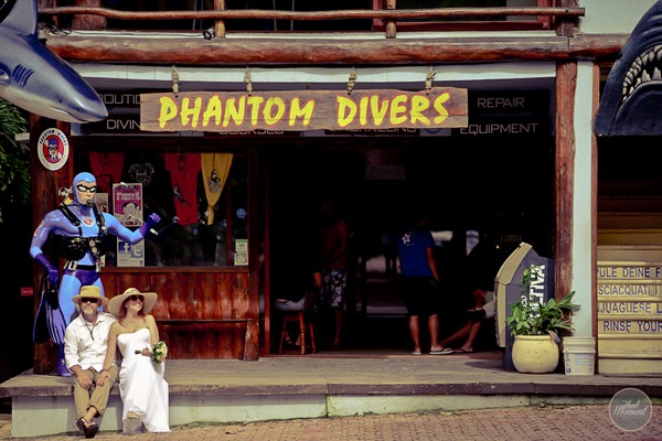 Bride and groom sitting outside Phantom Divers in Mexico