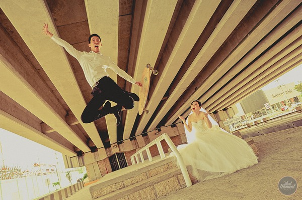 Groom jumping off skateboard as bride watches