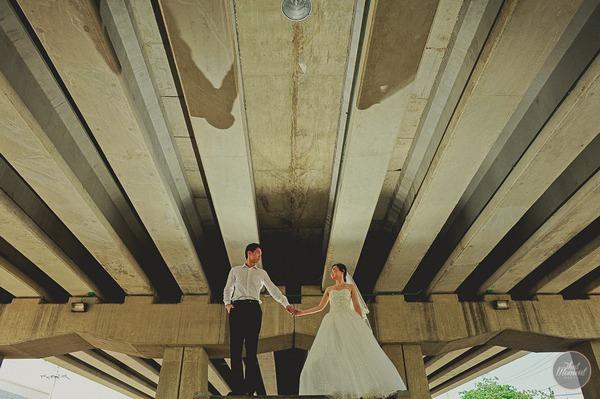 Bride and groom holding hands under bridge
