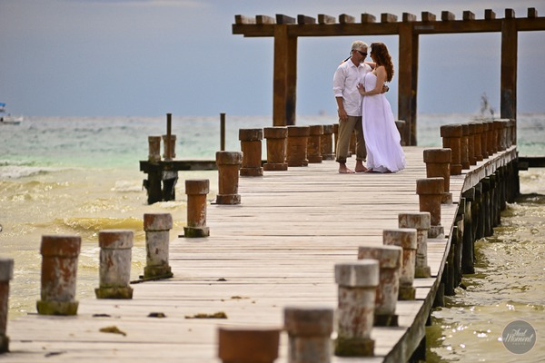 Bride and groom walking along jetty