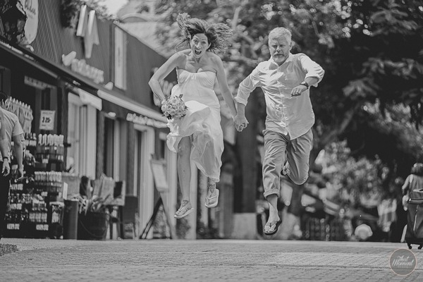 Bride and groom jumping in street