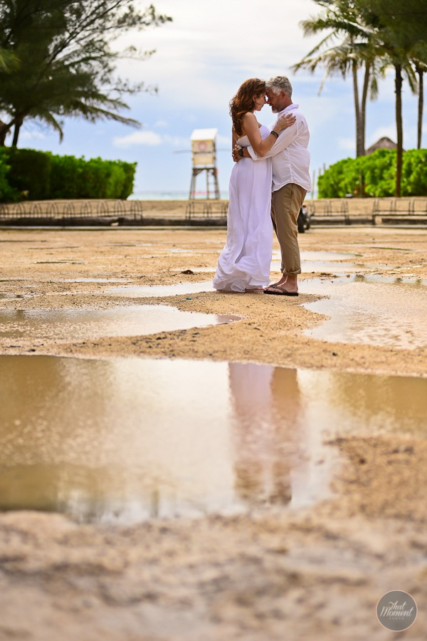 Bride and groom standing by puddle