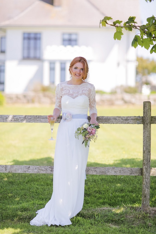 Bride leaning against fence