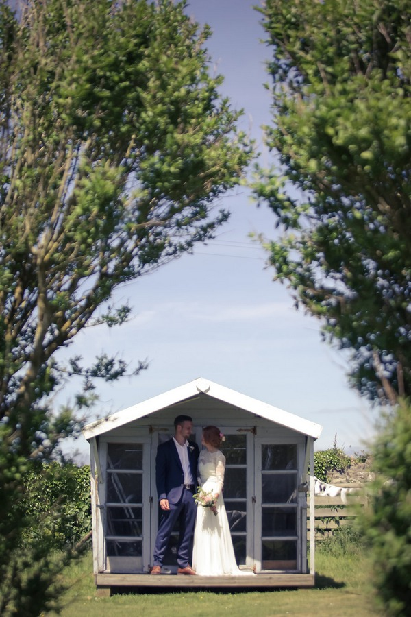 Bride and groom standing outside summer house