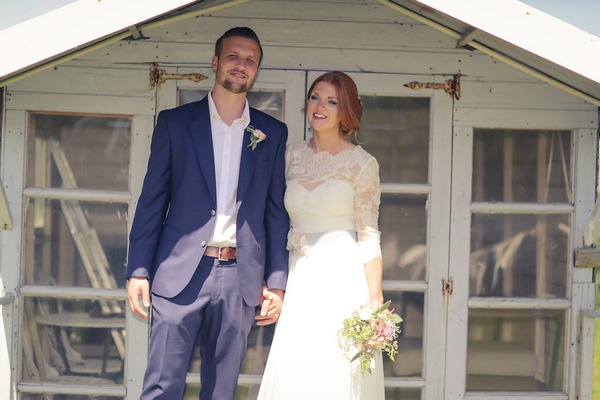 Bride and groom outside summer house