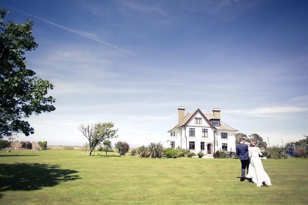Bride and groom walking across grounds of BoHo Cornwall