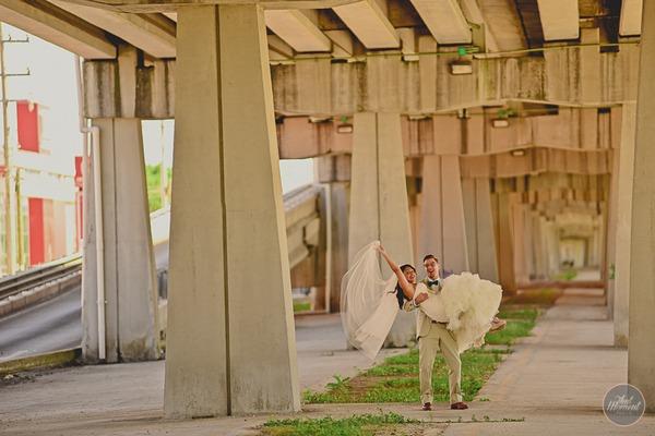 Groom carrying bride under bridge for post wedding shoot