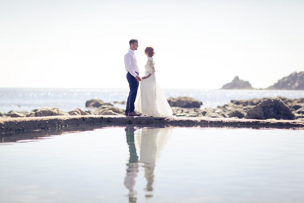 Bride and groom on rocks by sea in Cornwall