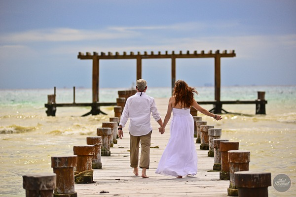 Bride and groom walking on beach holding hands