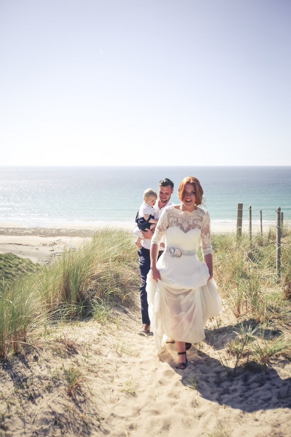Bride and groom walking along beach path in Cornwall