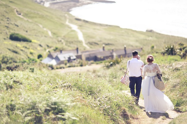 Bride and groom walking back from beach in Cornwall