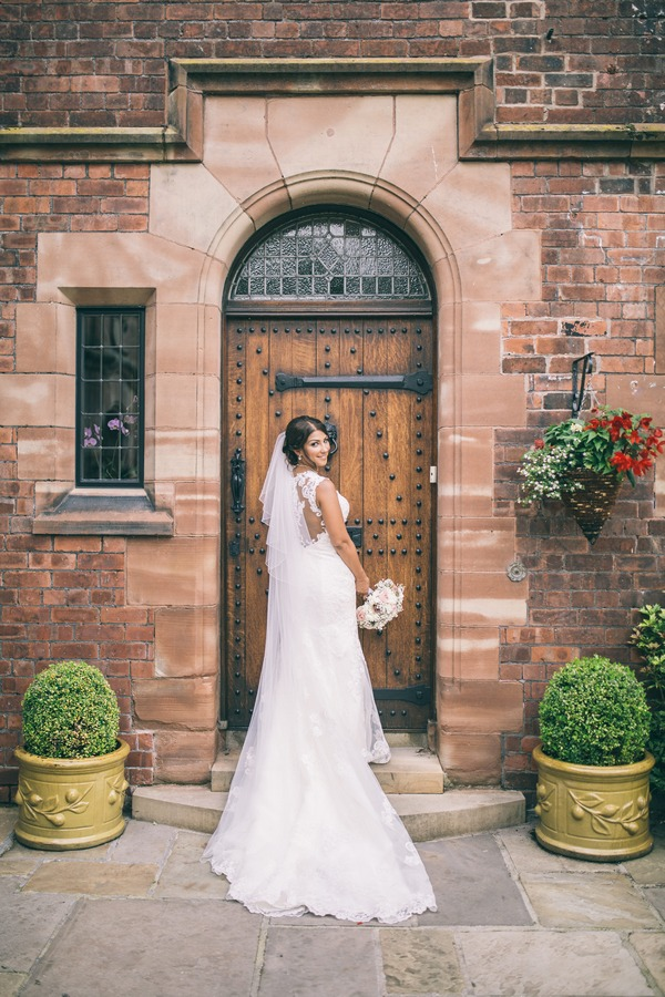 Bride in front of door looking over shoulder