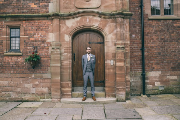 Groom standing in front of door at Colshaw Hall