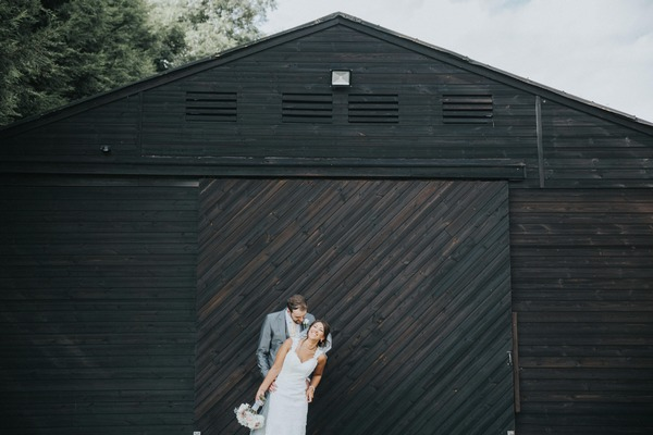 Bride and groom in front of large wooden building at Colshaw Hall