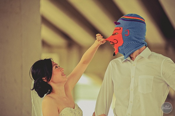 Bride pulling nose of groom's devil balaclava