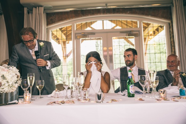 Bride hiding face with napkin during father of the bride wedding speech